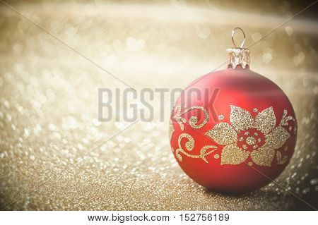 Red Christmas bauble on background of defocused golden lights. Red Christmas ball on golden blurred background