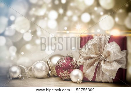 Red Christmas gift box and baubles on background of defocused golden lights. Red Christmas ball on golden blurred background
