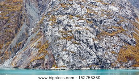 The panoramic view of a rocky coastline in early Autumn in Glacier Bay national park.