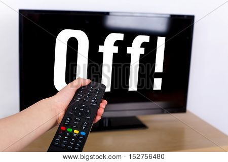 Hand using a remote control to turn off the TV with an OFF text on its screen