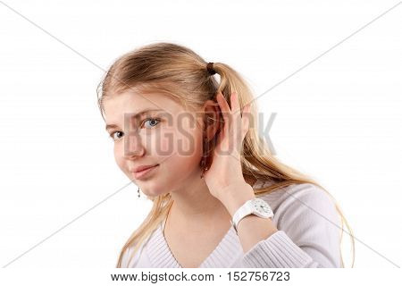 Young woman can't hear you - she cupping her hand behind her ear and listening. Studio isolated on white