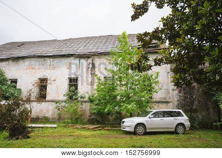 Batumi, Georgia - May 28, 2016: The White Car Mitsubishi Airtrek Outlander Parked On Grass Next To Old Abandoned Shabby Building, Surrounded By Green Trees.