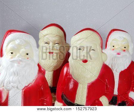 A quartet of vintage creepy plastic Santa Claus decorations for Christmas