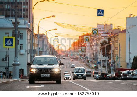 Gomel, Belarus  - July 30, 2016: Traffic On Lenin Avenue On The Sunset With Moving Black BMW X3 Car, Compact Luxury Crossover SUV Foreground. View Of Central City Street Going Straight To Lenin Square