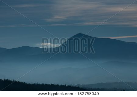 Morning Fog On The Mountain Slopes. Carpathian Mountains. Ukraine, Europe. Color Toning. Low Contras