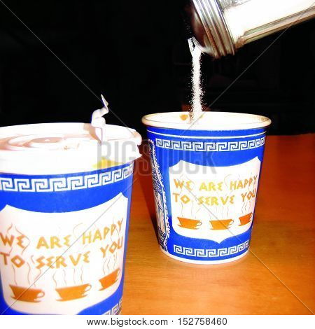 Pouring sugar into two take out paper coffee cups