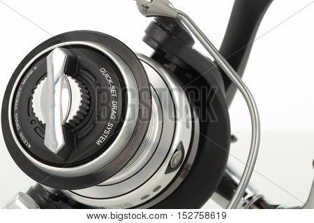 Black fishing reel isolated on white close-up