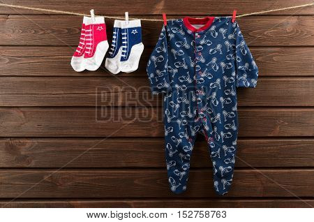 Baby boy clothes (sleepsuit and socks) hanging on the clothesline