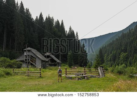 Man looking on old wooden house in the mountains