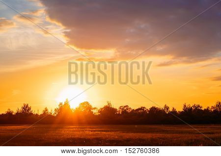Sunset, Sunrise Over Rural Meadow Field. Bright Dramatic Sky And Dark Ground. Countryside Landscape Under Scenic Summer Dramatic Sky In Sunset Dawn Sunrise. Skyline.
