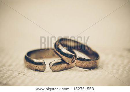 Two broken golden wedding rings / Divorce concept