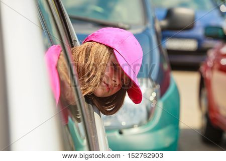 Summer holidays and leisure. Young little girl tourist in pink cap outdoors in car. Child looking out of window in transportation mobility vehicle.