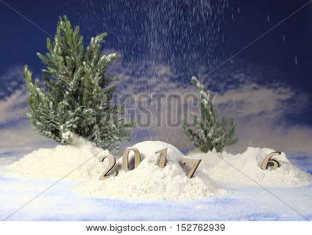new year 2017,figures of the coming new year in a snowdrift against the background of fir-trees and snowfall.christmas composition