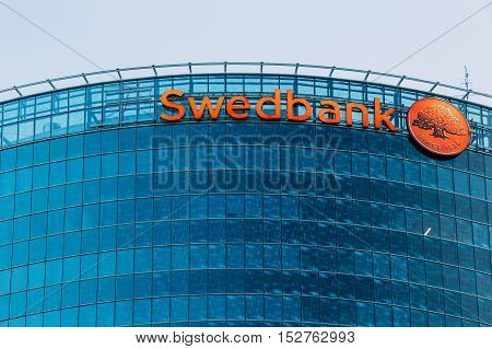 Riga, Latvia - June 30, 2016: Close View Of Blue Glass Building Facade Of Headquarter Of Swedbank With Red Signboard And Round Logotype On It.