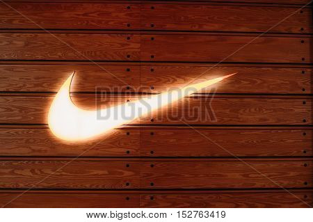 Vilnius, Lithuania - July 08, 2016: Close The Glowing Yellow Logotype Swoosh Of Nike Brand At Wooden Batten Wall Of The Store In Acropolis Shopping Center.