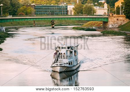 White Pleasure Boat With Passengers On Board Floation On Neris River Under Green Bridge In City Area In Vilnius, Lithuania