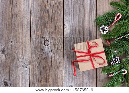Christmas holiday wooden background with fir branches and gift box on right border