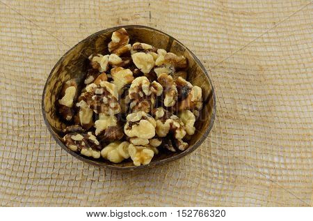 Shelled walnut halves and pieces in nut snack appetizer bowl