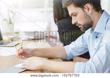 Handsome man is sitting at desk in office. He is writing his ideas in notebook with inspiration