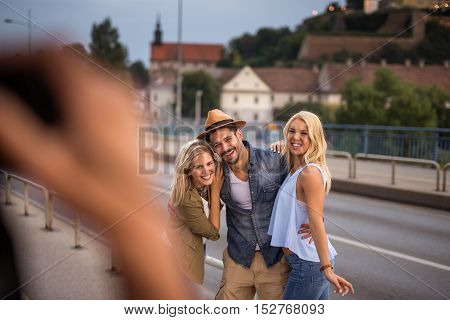Tourists enjoying city tour and photographing while traveling together.