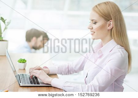 Beautiful young woman is typing on a laptop. She is sitting at desk and smiling