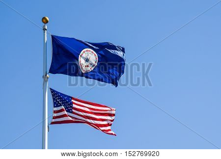 The flags of the United States and Virginia on poles during windy weather taken at the University of Virginia