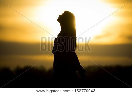Twilight silhouette by beautiful sunny young woman in summer. The sun stands at the horizon and the girl becomes a very nice black silhouette.