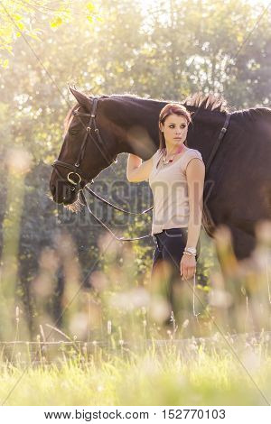 Wonderful young equestrian woman with horse in summer sun nature. Scene of a teenager horsewoman holding her best animal friend in a lovely sunny outdoor scene. Portrait format with copyspace.