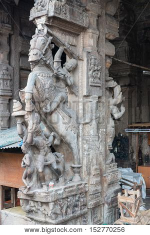 Madurai India - October 22 2013: Historic gray-stone statue of Nayak king on his horse in attacking mode. On pillar at entrance of Nagara Mandapam.