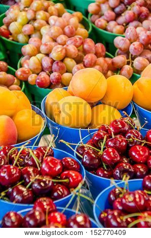 Fresh cherries, apricots and red grapes in pots on display at farmers market