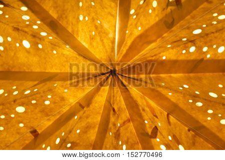 Orange golden background. Macro closeup of a shining star at xmas.