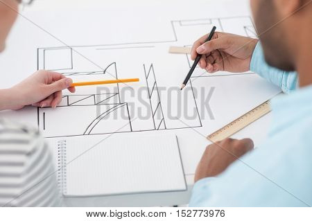 Drawing up plans. Top view of two successful architect reviewing blueprint and using pencils