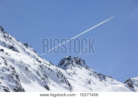 Plane Trail Over Snowy Mountain