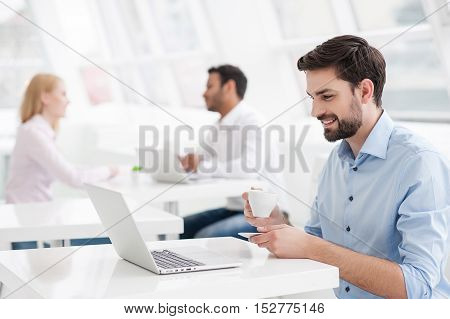 I love work environment. Smiling young male designer having coffee while sitting at his office desk with colleagues working in background