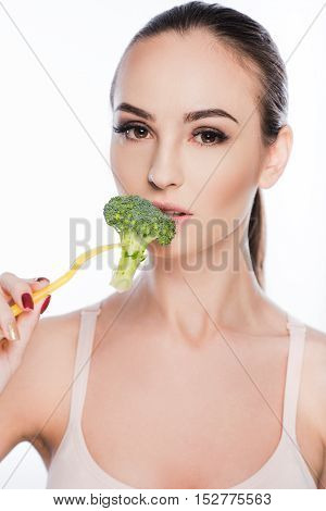 Healthy young woman is eating broccoli with enjoyment. Isolated