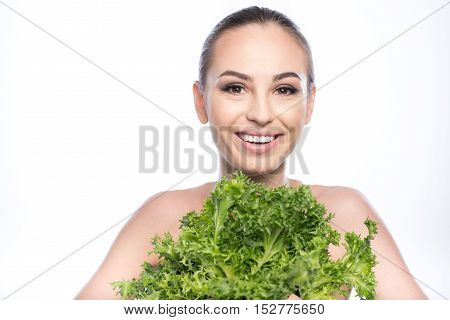 I like healthy diet. Slim naked girl is standing and holding lettuce. She is laughing. Isolated and copy space in left side
