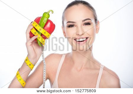 Vegetables will make you fit. Cheerful girl is holding peppers with tape and smiling. She is standing and looking at camera with satisfaction. Isolated on background