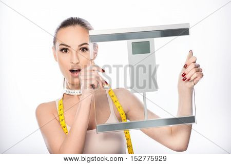 Successful weight loss. Excited young woman is standing and showing balance. She is holding tape and looking at camera with shock. Isolated