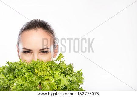 Joyful young girl is covering her mouth by lettuce. She is looking at camera with confidence. Isolated and copy space in right side