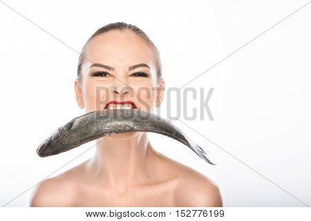 Greedy young girl is holding raw fish in mouth. She is standing and looking forward with aggression. Isolated and copy space in right side