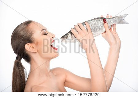 Hungry woman is holding fish and opening mouth with appetite. She is standing with naked shoulders. Isolated