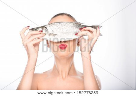 Pretty girl is holding fish and covering eyes with it. She is standing and sending kiss to camera. Isolated
