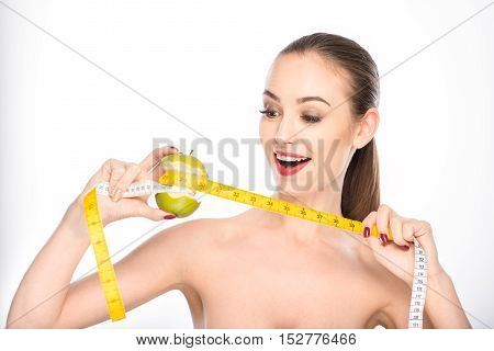 Wonderful result of healthy diet. Excited young woman is taking measurements of bitten apple waist and smiling. Isolated