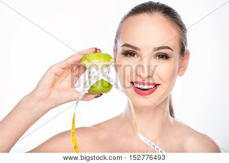 Eating fruits is the best diet. Healthy woman is measuring bitten apple by tape. She is showing result to camera and smiling. Isolated