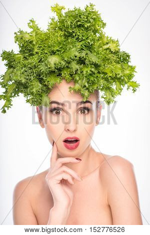 Healthy girl is holding lettuce on her head. She is standing and looking at camera with surprise. Isolated