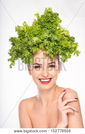 I like this diet. Happy young woman is standing with lettuce on her head. She is looking at camera with smiling. Isolated