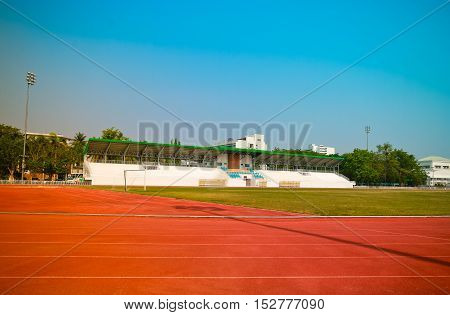 Red treadmill track running at the stadium with green grass on blue sky