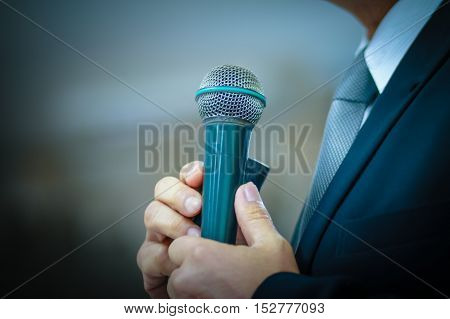blurred of businessman speech with microphone in meeting room