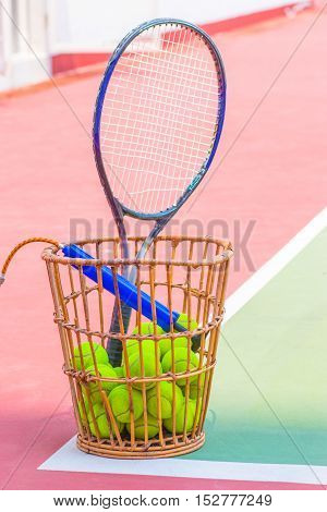 Tennis Ball with Racket on basket tennis court