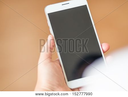 smartphone with white black screen display on hand brown background